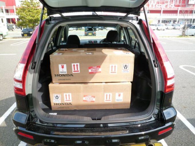 USヘッドライトが梱包されたダンボールを車に積んでいる