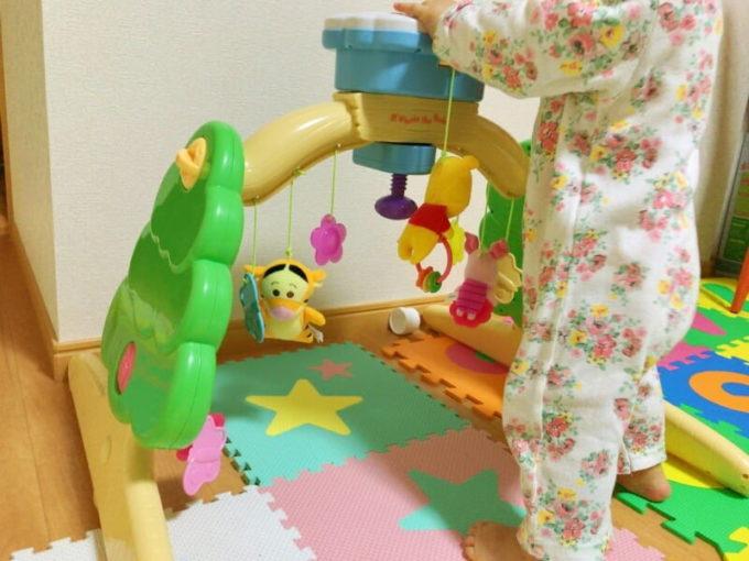 床に置いたメリーにつかまり立ちする子供
